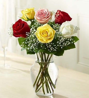 six roses arranged in a glass vase