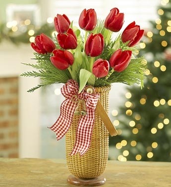 red tulips with evergreen in cylinder vase